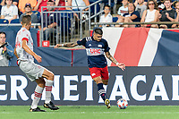 FOXBOROUGH, MA - JULY 7: Gustavo Bou #7 of New England Revolution crosses the ball during a game between Toronto FC and New England Revolution at Gillette Stadium on July 7, 2021 in Foxborough, Massachusetts.
