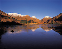 Snow-covered distant summits of the Glencoe mountains reflecting in the frozen surface of the River Etive, Glen Etive, Scottish Highland