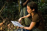 African Golden Cat (Caracal aurata aurata) biologist Laila Bahaa-el-din and Arthur Dibambo planning out route on map, Lope National Park, Gabon