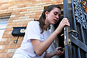 Tulane freshmen Rebekah Oviatt removes a screen while volunteering with South Seventh Ward Neighbors, 2016.