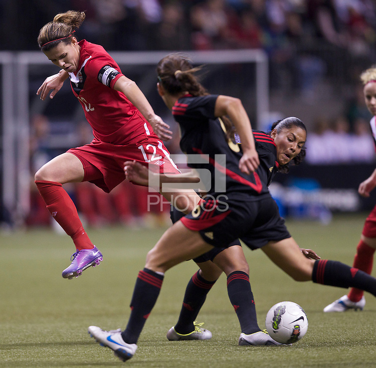 Christine Sinclair, left, of Canada tries to get past a pair of Mexico defenders in the CONCACAF Olympic Qualifying semifinal match at BC Place in Vancouver, B.C., Canada Friday Jan. 27, 2012. Canada won the match 3-1 to earn a berth in 2012 London Olympics.
