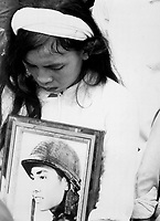 """Almost 400 men, women and children massacred by the Viet Cong during """"Tet 1968"""" were mourned at a common-grave burial on October 14.  This young widow, carrying a photograph of her missing husband, mourns at the mass funeral service.  Hue, 1968.  (USIA)<br /> NARA FILE #:  306-MVP-4-8<br /> WAR & CONFLICT BOOK #:  427"""