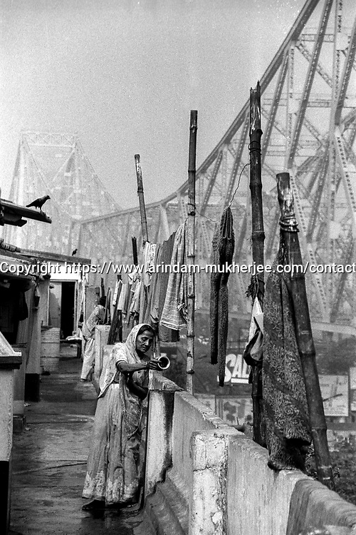 An old lady prays on a roof near Horah Bridge over river Ganga in Kolkata, India.
