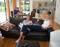 23-06-10, Tennis, England, Wimbledon, Caroline Wozniacki photoshoot, Caroline relaxes on the couch of their house in Wimbledon with mother Anna, her brother Patrik in the background.