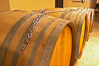 A row of demi muid barrels in the wine cellar used for aging the wine in oak with a metal stick and chain (baton) used for stirring the lees (batonnage), Champagne Jacquesson in Dizy, Vallee de la Marne, Champagne, Marne, Ardennes, France