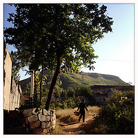 A man walks through a small Chinese village while carrying a basket.