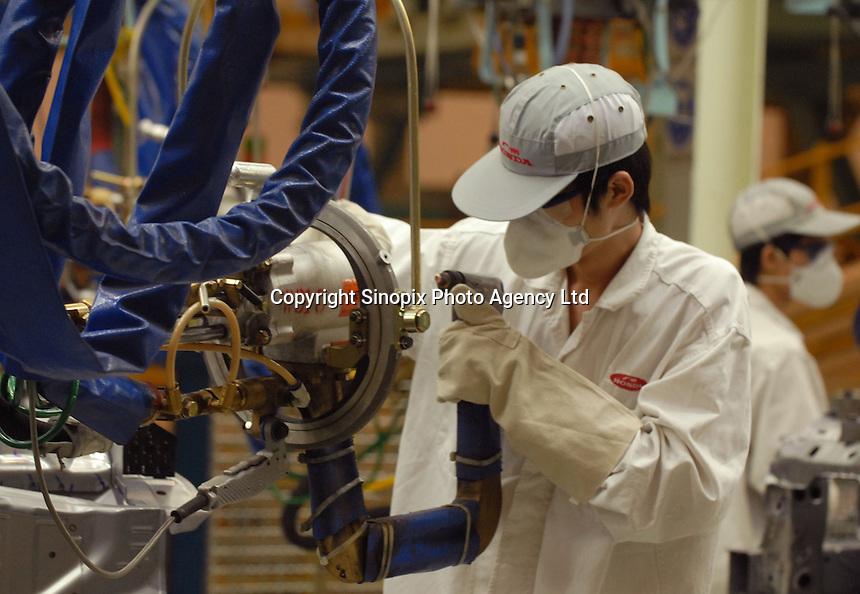 A worker with a high-tech welding gun at the new Guangzhou Honda Automobile Co. Ltd factory. The plant built at a cost of 140 million US$ is one of the most advanced car plants in the world. It has a state of the art production line as well as the world's first total water re-cycling sytem..