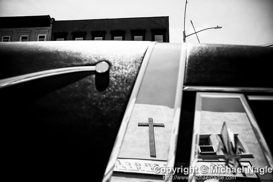 A cross is reflected in a hearse at the funeral for one year-old Davell Gardner Jr. at Pleasant Grove Tabernacle on July 27, 2020 in the Brooklyn borough of New York City.  Gardner was shot and killed earlier this month during a cookout in front of his home along with three others.  Photograph by Michael Nagle