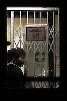 Il vetro rotto all'entrata del centro e dietro un rifugiato<br /> Broken glasses and a refugee behind it<br /> Roma 12-11-2014 Tor Sapienza. Nella serata di ieri, dopo una manifestazione avvenuta nel pomeriggio, un centinaio di abitanti del quartiere, hanno lanciato sassi e bombe carta verso il centro di accoglienza per rifugiati di via Morandi, aperto nel loro quartiere. All'arrivo di un ingente dispiegamento di forze dell'ordine, gli abitanti hanno bruciato dei cassonetti per sbarrare la strada ed hanno tirato verso gli agenti oggetti vari dalle finestre, tra i quali e' stato rinvenuto un coltello da cucina, generando una vera e propria guerriglia urbana. 4 poliziotti sono rimasti feriti e sono state danneggiate macchine della polizia. La polizia si e' infine schierata a protezione del centro di accoglienza. <br /> In Rome's Tor Sapienza quarter, where 36 immigrants live, one hundred people tried to enter the center, throwing home made bombs, to chase away the immigrants. When the police arrived, the inhabitants burned garbage bins and throw objects from windows, among them a cooking knife. In the end the police trooped in front of the immigrant center to protect it.<br /> Photo Samantha Zucchi Insidefoto