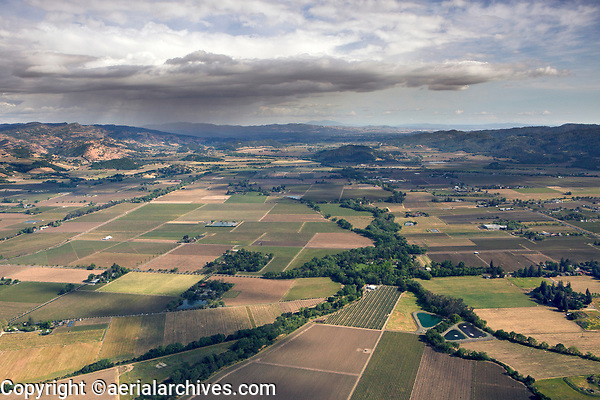 aerial photograph of Napa Valley from Rutherford  toward the Yountville Hills; storm clouds pass to the south, Mount Diablo in the distant horizon, Napa River foreground left, Bale Slough foreground right