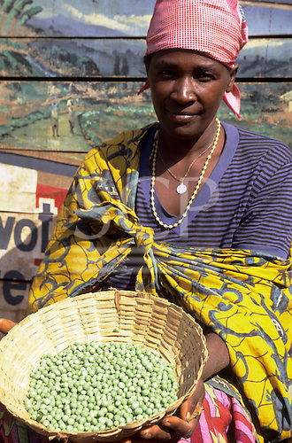Gitega, Burundi. Woman in the market selling peas and fruit in front of a painted wall with pictures; French words.