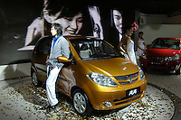 Models perform beside a Changan BenBen, the first self-designed compact car of Changan Automobile,  during the 2006 International Automotive Exhibition in Beijing, China..