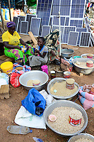 BURKINA FASO, Provinz Poni, Gaoua, weekly market with food crops and solar panels, girl playing with mobile phone /Gaoua, Markt, Verkauf Erdnuesse, Bohnen, Reis, Stand mit Solar Modulen, Maedchen mit Mobiltelefon