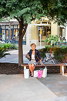 Attractive female shopper texting on her smartphone with shopping bags at an Austin outdoor shopping mall