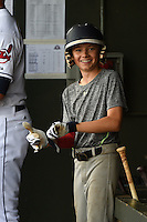 Peoria Javelinas batboy puts on gloves given to him by Francisco Lindor (not shown) during an Arizona Fall League game against the Scottsdale Scorpions on October 18, 2014 at Surprise Stadium in Surprise, Arizona.  Peoria defeated Scottsdale 4-3.  (Mike Janes/Four Seam Images)
