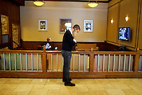 John Favreau, Barack Obama's Chief Speech Writer, at work on his victory speech for tonight's primary election, in a hotel lobby. Playing on the television is President Bush.