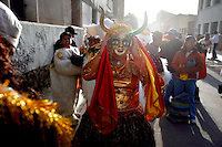 A girl puts on her mask as she prepares to dance in Oruro at the Carnaval de Oruro. During the fiesta many people sacrifice llamas and give offerings such as coca leaves and cigarettes to show their dedication to the Devil, a Virgin, Pachamama or Mother Earth. The Devil (or Uncle) is a mythical character that protects the miners of Oruro who work in dangerous conditions hundreds of metres below the ground. During the carnival, people dress in outrageous costumes and dance for days before arriving at the Church of Socavon, where they pay their respects to a virgin. Ironically, many of the dancers wear devil costumes.
