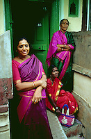 An Indian street scene in which three women in colorful saris pose in a doorway. Bangladore, India.