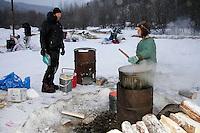 Thursday March 8, 2007   ----  Ray Redington Jr. gets hot water made by the Takotna residents as Bill Pinkham waits his turn at Takotna on Thursday morning.