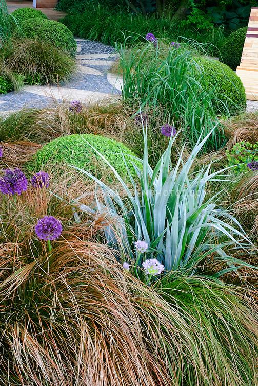Astelia, Allium, ornamental grass, Buxus, garden chair furniture, patio, Euphorbia, for a brown and green and purple soothing garden color planting tones, stone garden path patio, deck