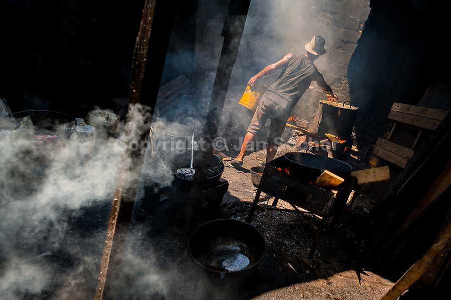 An Afro-Colombian cook fries fish in boiling oil in a street restaurant in the market of Bazurto in Cartagena, Colombia, 16 December 2017. Far from the touristy places in the walled city, a colorful, vibrant labyrinth of Cartagena's biggest open-air market sprawls to the Caribbean seashore. Here, in the dark and narrow alleys, full of scrappy stalls selling fruit, vegetables and herbs, meat and raw fish, with smelly garbage on the floor and loud reggaeton music in the air, the African roots of Colombia are manifested.