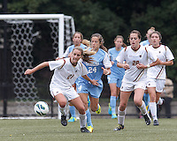 Boston College midfielder Kate McCarthy (21) works to clear ball as University of North Carolina midfielder Paige Nielsen (24) closes.  University of North Carolina (blue) defeated Boston College (white), 1-0, at Newton Campus Field, on October 13, 2013.