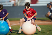 A young fan competes in a giant bouncing ball race between innings of the Southern Collegiate Baseball League game between the Carolina Venom and the Mooresville Spinners at Moor Park on June 22, 2020 in Mooresville, NC.  The Spinners defeated the Venom 7-2. (Brian Westerholt/Four Seam Images)