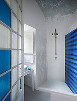 A glass-paned door opens into this small bathroom created in a restored convent: a combination of ancient and modern