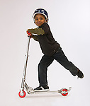 Children posed on a toy scooter on a white background.