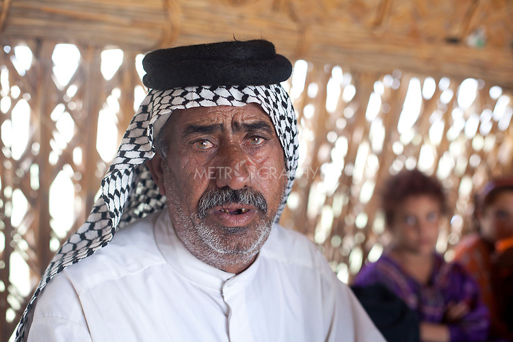 AL-SELKHA, IRAQ: Sfah Jabr and his family sit in a traditional reed house in the village of Al Selkha...Dozens of families displaced by years of violence live in the village of Al Selkha in Nasiriya...Photo by Ali Arkady/Metrography