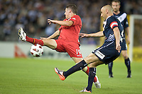 MELBOURNE, AUSTRALIA - OCTOBER 30: Mathew Leckie of United attempts to block a kick by Kevin Muscat of the Victory during the round 12 A-League match between the Melbourne Victory and Adelaide United at Etihad Stadium on October 30, 2010 in Melbourne, Australia.  (Photo by Sydney Low / Asterisk Images)