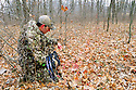 00105-051.20 Bowhunting: Archer examines blood trail on leafy forest floor.  Hunt, track, spoor, wound.