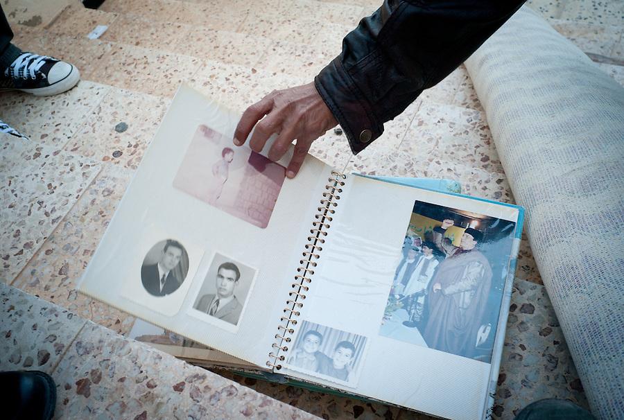 Anti-Gaddafi fighters flip through a photo album found in an abandoned private home in Sirte, Libya.
