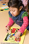 Educaton preschool  3-4 year olds girl playing with wood puzzle on table vertical