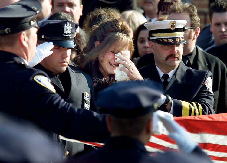 (MEMORIAL MASS)--24393--On Fri Nov 16,2001--memorial1116a-- Cindy Rodriguez (center) weeps as an American Flag is folded in front of her in honor of her husband PAPD Police Officer Richard Rodriguez in front of the Holy Spirit RC Church, Perth Amboy after a memorial mass for her husband Port Authority Police Officer Richard Rodriguez whom remains missing from the Sept. 11th attack at the World Trade center.  Cindy is supported by her brother (left0 Jersey City Police Officer James Lisi and Larry Cattano, Perth Amboy's Fire Chief who is Richard's best friend.(MAKR R. SULLIVAN/HNT CHIEF PHOTOGRAPHER)