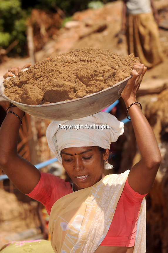A young female worker carries soil at the construction site in Madras, India
