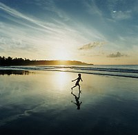 Boy Walking Next To His Reflection On A Beach Near Tangalle, Sri Lanka