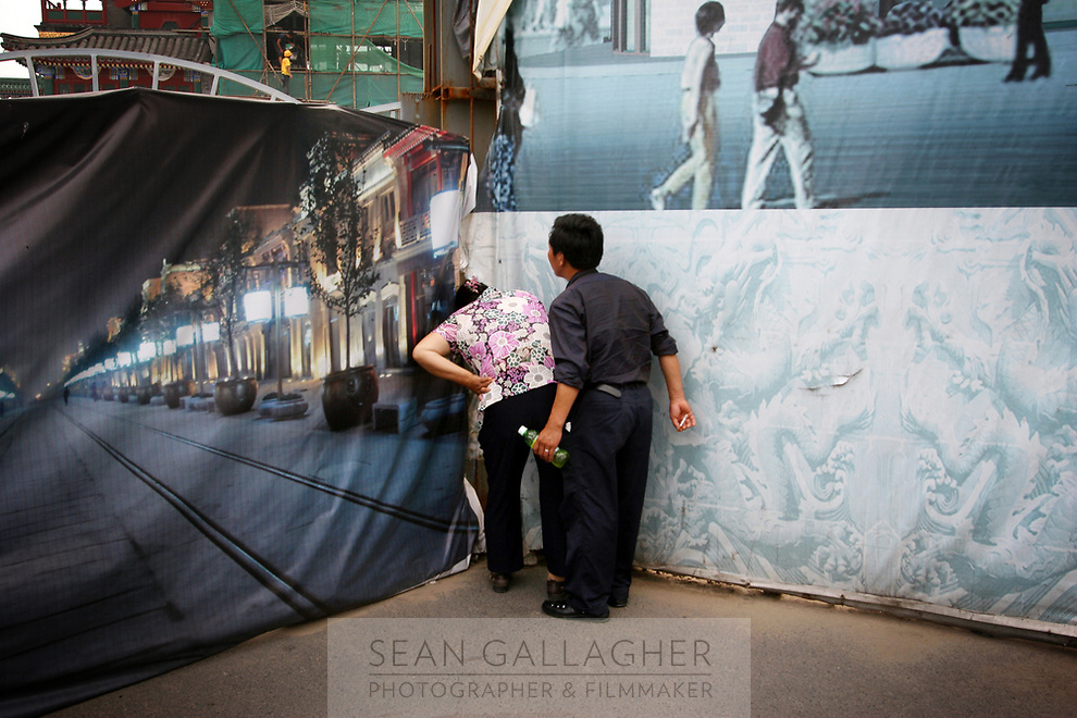 """CHINA. Beijing. A couple peer through a fence, trying to catch a glimpse of the new Qianmen shopping district. In recent years construction has boomed in Beijing as a result of the country's widespread economic growth and the awarding of the 2008 Summer Olympics to the city. For Beijing's residents however, it seems as their city is continually under construction with old neighborhoods regularly being razed and new apartments, office blocks and sports venues appearing in their place. A new Beijing has been promised to the people to act as a showcase to the world for the 'new' China. Beijing's residents have been waiting for this promised change for years and are still waiting, asking the question """"Where's the new Beijing?!"""". 2008"""