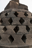 Borobudur, Java, Indonesia.   Close-up of a stupa on the upper level of the temple.  The diamond-shaped holes symbolize the passions that still linger as men rise toward Nirvana.
