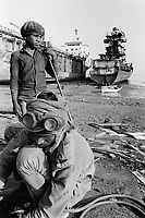 India. Province of Gujarat. Alang. A man and a young boy, both are workers and stand on the beach. Child labour. Ships aground. Vessels stranded. Bottoms of ships at low tide on the shore. Alang, located in the Gulf of Khambhat, is a ships breaking place and is considered as the biggest scrapyard in the world. Ships recycling for its metals. Environmental issues. Hazardous waste. © 1992 Didier Ruef
