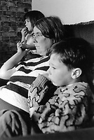 England. Greater Manchester. Salford. Women living in poverty. Ann and two of her seven children are seated on a couch in their flat's living room. They all watch a television program. The family is living on social security contributions. Salford is a city in the Metropolitan Borough of Salford in Greater Manchester. North West England is one of nine official regions of England. © 1990 Didier Ruef