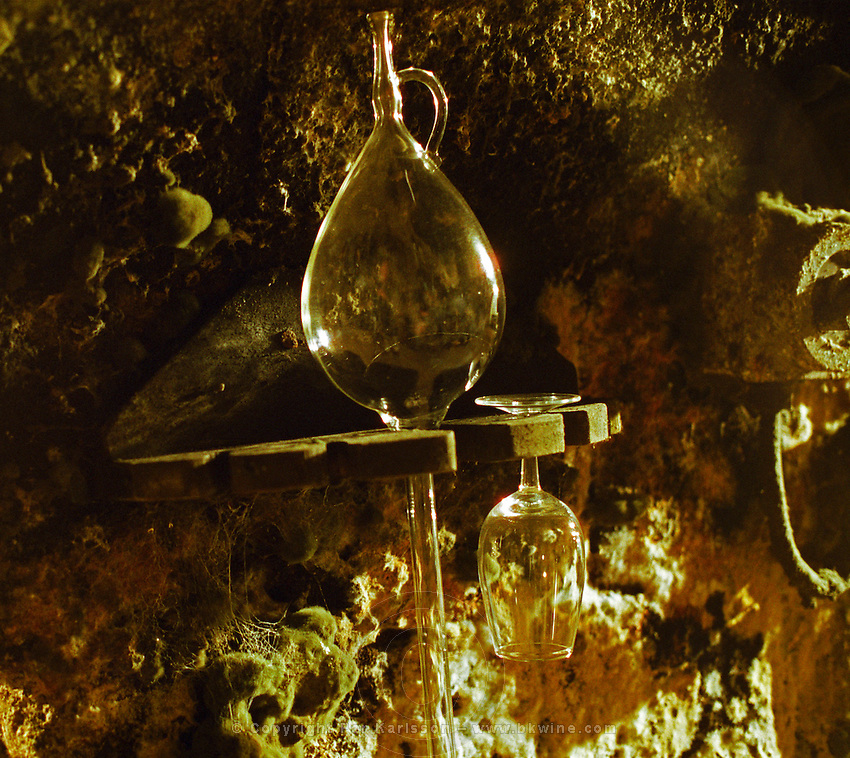 """The Royal Tokaji Wine company in Mad: the wine cellar with long tunnels filled with wooden barrels with ageing Tokaj wine - a glass pipette to take samples from the barrels and a tasting glass hanging on a mouldy wall. The RTWC in was one of the first Tokaj wineries to be """"revived"""" by an injection of foreign capital. It makes wine in a traditional style. Credit Per Karlsson BKWine.com"""