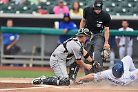 Jackson Generals catcher Marcus Littlewood (4) tags out a hard sliding Billy McKinney (4) as home plate umpire Alex MacKay prepares to make a call during a game against the Tennessee Smokies at Smokies Stadium on July 5, 2016 in Kodak, Tennessee. The Generals defeated the Smokies 6-4. (Tony Farlow/Four Seam Images)