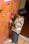 Education preschoool children ages 3-5 start of day boy putting his attendance card in slot vertical