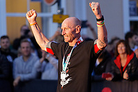 Pictured: Gareth Thomas celebrates as he crosses the finish line. Sunday 15 September 2019<br /> Re: Ironman triathlon event in Tenby, Wales, UK.