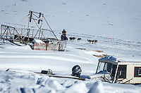 Ketil Reitan runs down the Yukon River past a fish-wheel and boats on the bank as he approaches the Nulato checkpoint on Saturday March 12th during the 2016 Iditarod.  Alaska    <br /> <br /> Photo by Jeff Schultz (C) 2016  ALL RIGHTS RESERVED