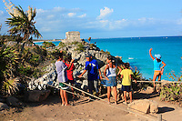 In Tulum in the Yucatan, young Mayas dressed in western clothing visit the famous archaeological site. Born in the cities, many young people no longer speak their vernacular tongue.
