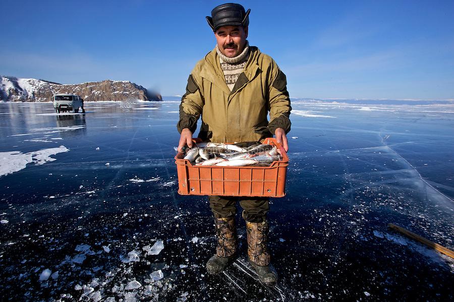 Fishermen  dragging huge nets trough ice holes cut by chainsaws. Tey catch olmu, an endemic fish of te Baikal and the staple food of the lake..Pêcheurs remontant leurs filets posés entre deux trous forés dans la glace. ils pechent l'omoul, un poisson endémique, emblématique du lac Baikal. On le mange grillé, fumé, salé, gelé et même cru. .