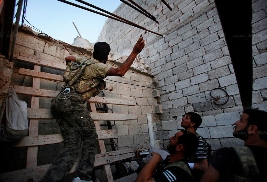 A Free Syria Army soldier throws a home-made grenade at Assad forces during urban fighting in the al-Amaria district of Aleppo...© Javier Manzano