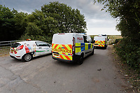 Pictured: Police vans at the scene.<br /> Re: A Bomb Disposal Unit was called after a bomb was discovered at a scrap yard in Skewen near Neath, and then transported to Crymlyn Burrows beach for a controlled explosion in south Wales, UK.